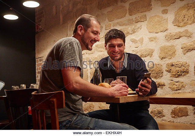 Two men having lunch in restaurant, one man showing the other his smartphone screen - Stock Image