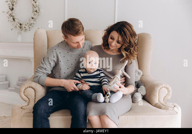 Caucasian mother and father sitting on love seat with baby son - Stock-Bilder