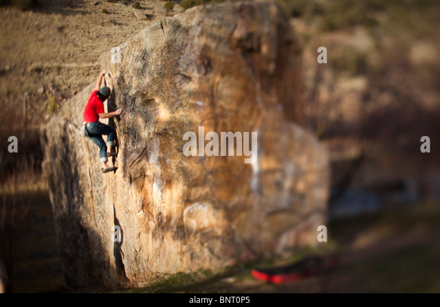 A rock climber works on bouldering problem in Colorado. - Stock Image
