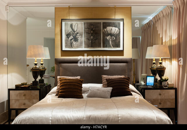 Botanical illustrations above double bed with matching bedside lamps and recessed mirrored walls in UK home - Stock Image