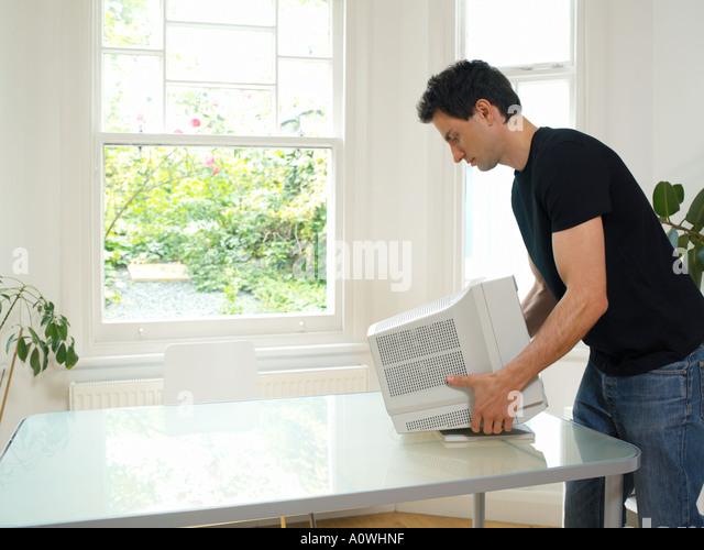 Man moving computer monitor - Stock Image