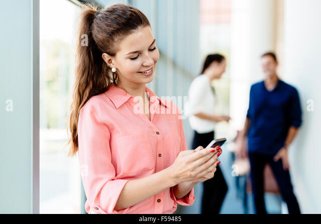 Beautiful women, colleagues using phones and talkin during break - Stock-Bilder