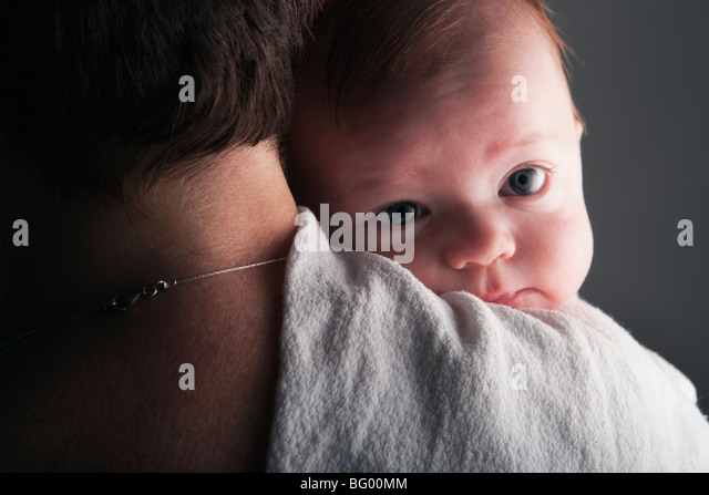 Young baby on mother's shoulder - Stock Image
