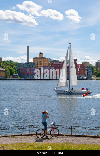 Woman with bicycle watching a sailing boat in the inlet to Stockholm, Sweden. - Stock Image