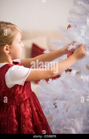 Little girl decorating white christmastree - Stock Image