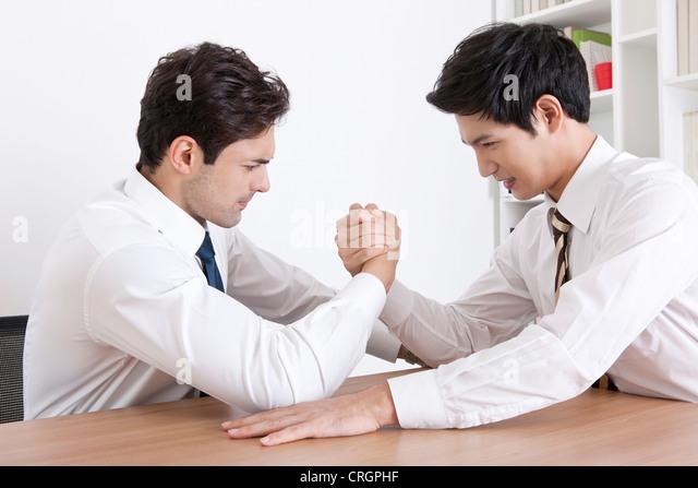Businessmen doing arm-wrestling in the office - Stock Image