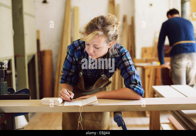 Young craftswoman making notes in pipe organ workshop - Stock Image