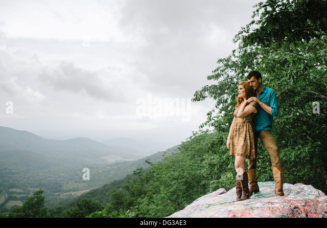 Young Couple Standing on Rock Ledge While Enjoying Scenic View - Stock-Bilder