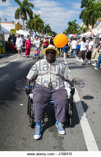 Miami Florida Little Havana Calle Ocho Street Festival Hispanic annual event celebration Black man disabled wheelchair - Stock Image