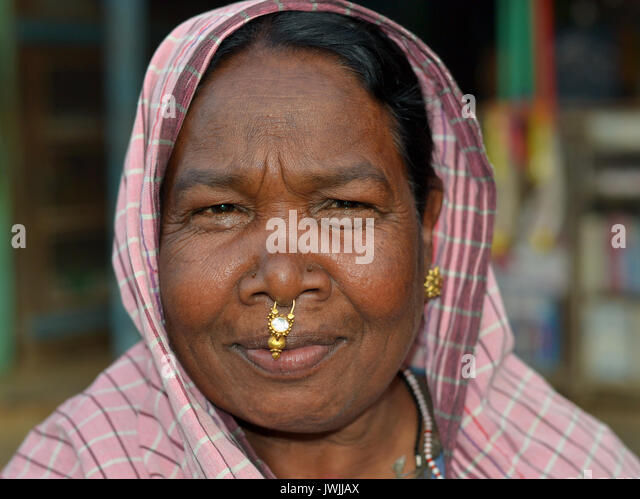 Closeup street portrait (outdoor headshot, seven-eighths view) of an overweight, mature Indian Adivasi market woman - Stock Image