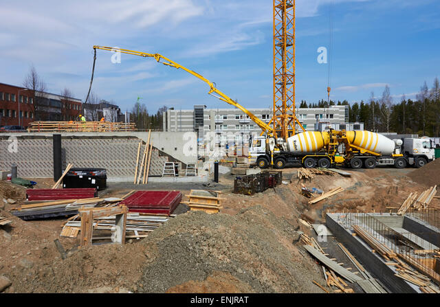 Building under construction with trucks delivering concrete, Finland - Stock Image