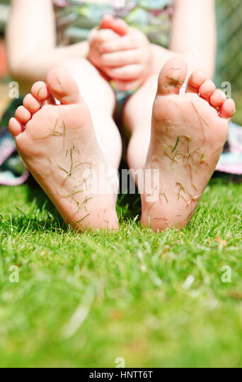 Four year old girl in a garden with grass cuttings on the soles of her feet. - Stock Image