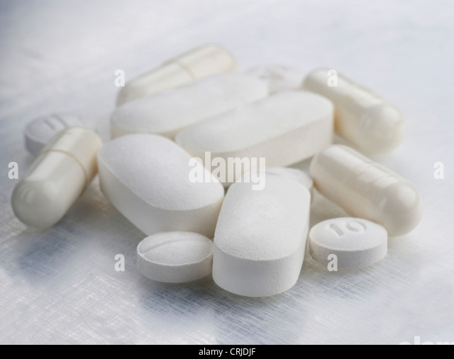 white pills on textured background - Stock Image