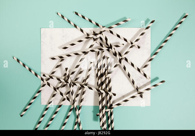 numerous straw on marble and turquoise color background - Stock Image