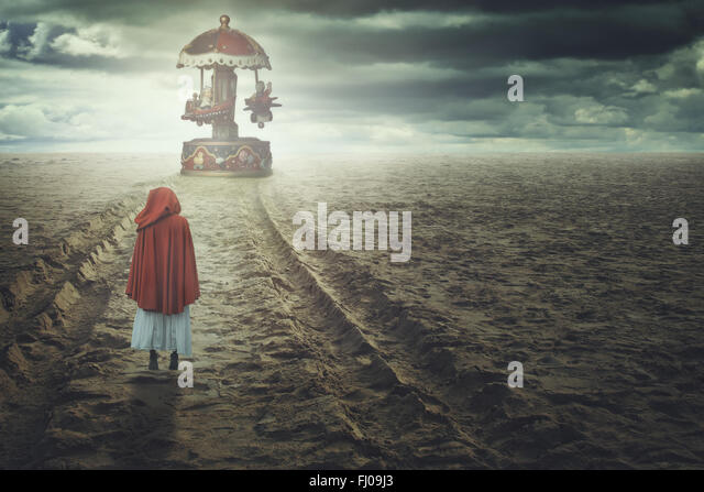Red hooded woman on a strange beach with toy carousel. Fantasy and surreal - Stock-Bilder