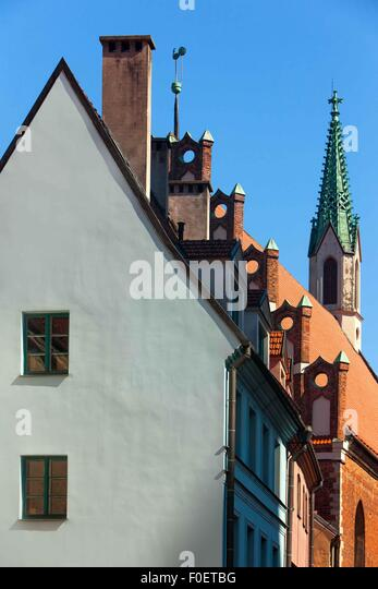 The facade of the old house and the green spire of the ancient church on a cockerel weather vane in Riga - Stock Image