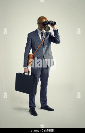 Businessman with gas mask  looking through binoculars - Stock Image