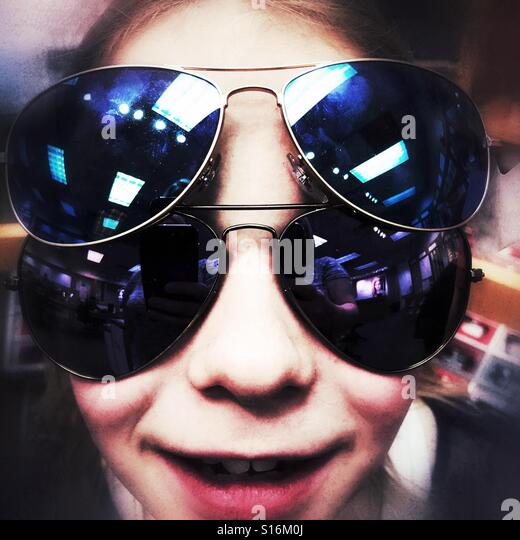A bug-eyed girl playing with sunglasses. - Stock Image