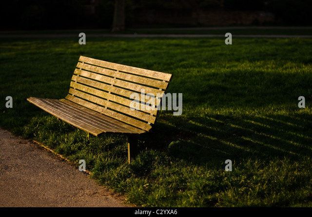 A park bench in Primrose Hill, London, casts a shadow in the evening light - Stock Image