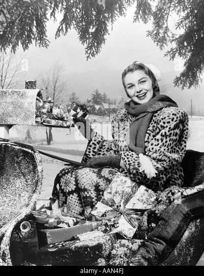 1950s SMILING WOMAN LOOKING AT CAMERA RIDING IN SLEIGH WEARING  LEOPARD SKIN FUR COAT AT MAILBOX WITH PACKAGES - Stock Image