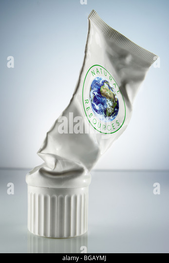 squeezed-out white tube marked with the words natural resources and a globe - Stock Image