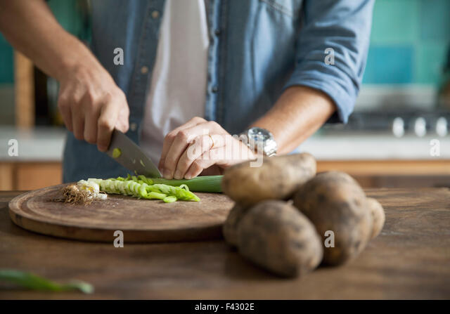 Man cutting spring onion in kitchen - Stock Image