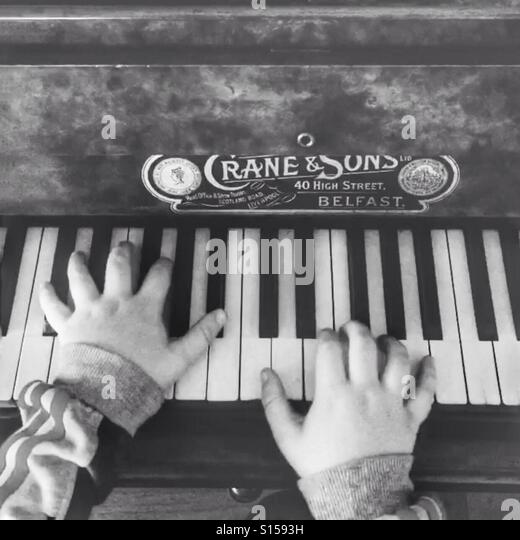 Black and white image of young child playing piano - Stock-Bilder