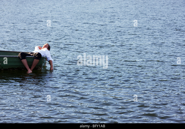 businessman relaxing in rowboat - Stock Image