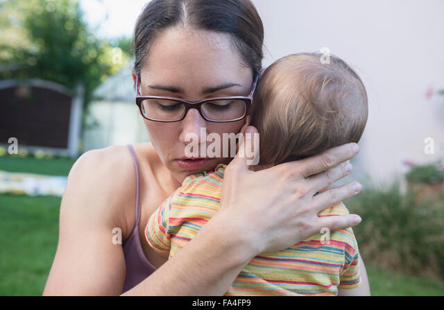 Mother comfort her baby son in a lawn, Munich, Bavaria, Germany - Stock Image
