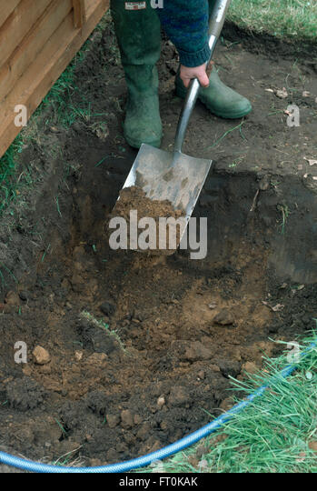 Close-up of a gardener digging up turf to make a new border - Stock Image