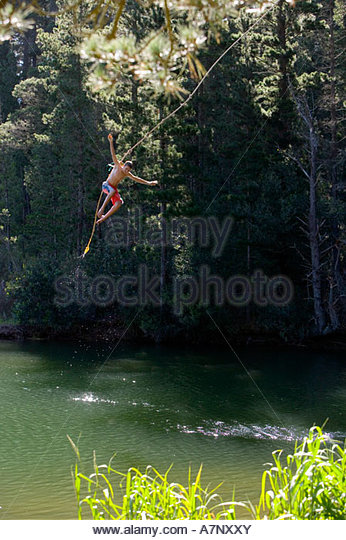 Boy 9 11 in swimming shorts letting go of rope swing above lake - Stock-Bilder
