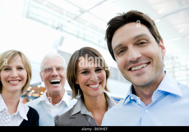 4 happy people looking at viewer - Stock Image