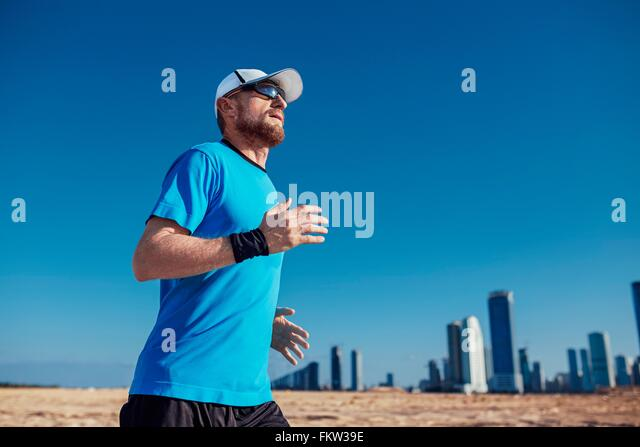 Low angle view of mid adult man running by skyscrapers, Dubai, United Arab Emirates - Stock Image