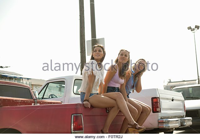 Three young women, sitting on back of truck, looking away - Stock Image
