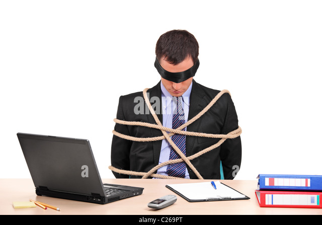 A businessman tied up with rope in his office - Stock Image