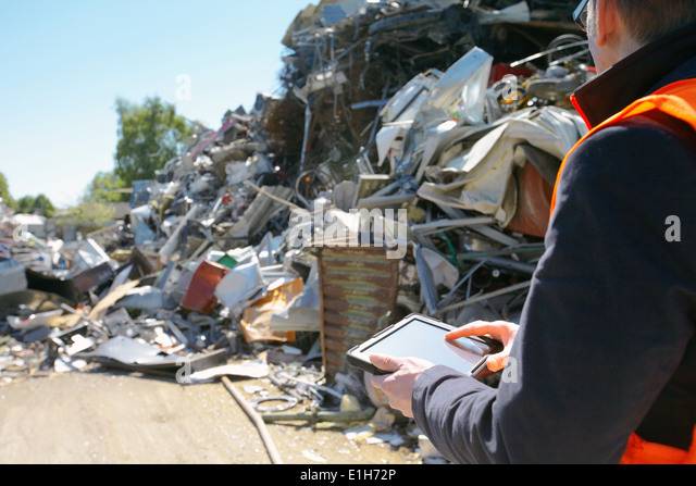 Foreman using digital tablet at scrap metal recycling plant - Stock Image