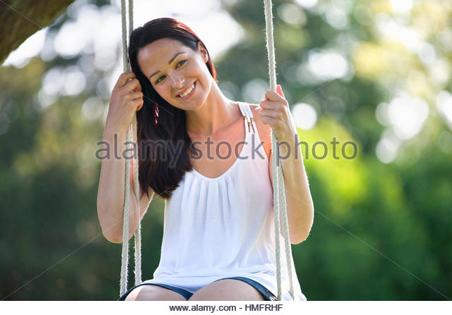 Portrait happy brunette woman swinging on swing in summer yard - Stock-Bilder