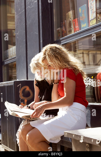 Two friends using a map Copenhagen Denmark. - Stock Image