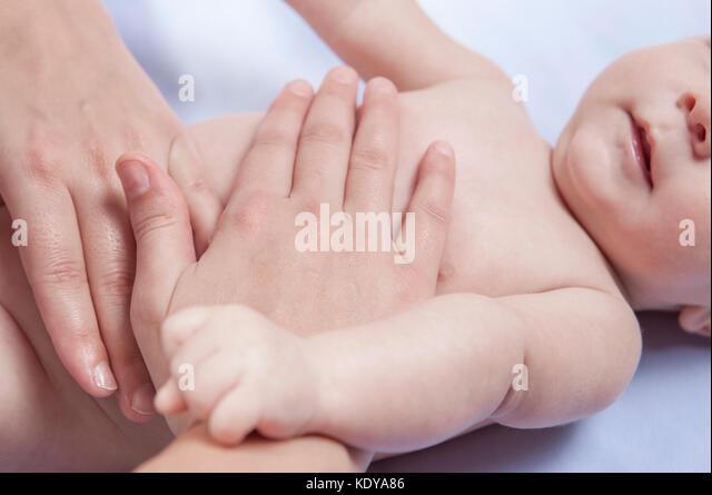 Three month baby boy receiving abdomen massage from a female massage therapist - Stock Image