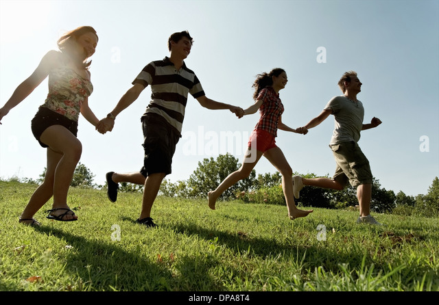 Group of young adults holding hands and running - Stock Image