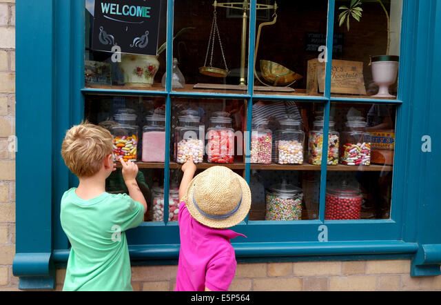 Children choosing sweets sweet shop window Blists Hill Victorian Town Uk - Stock Image