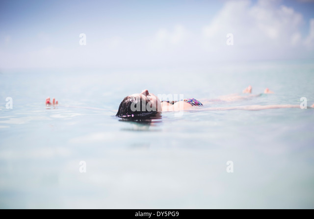 Woman floating in the sea - Stock Image