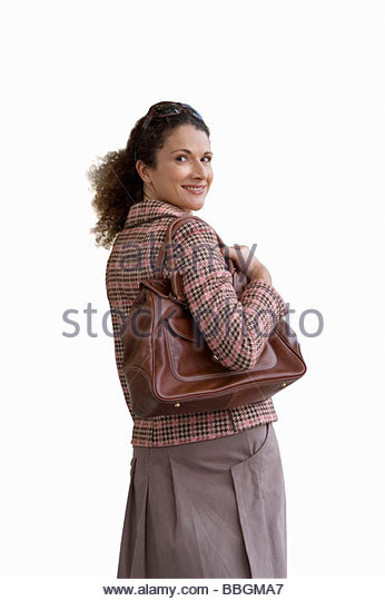 Woman with handbag looking into camera, cut out - Stock Image