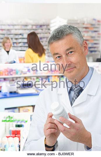 Pharmacist reading label on medicine bottle in pharmacy - Stock Image