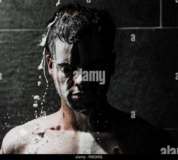 Young Man Bathing With Milk - Stock Image