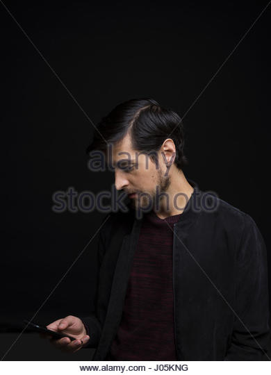 Brunette man with beard texting with cell phone against black background - Stock Image