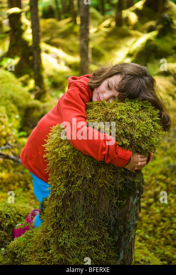 Girl hugging moss covered stump, Naikoon Provincial Park, Queen Charlotte Islands, British Columbia, Canada - Stock Image