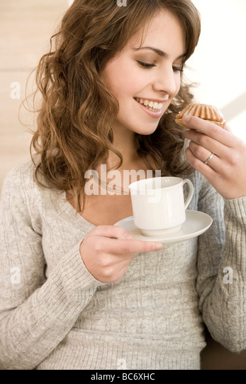 woman eating cupcakes at home - Stock-Bilder