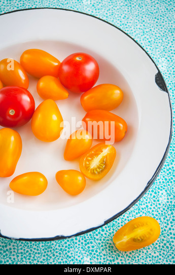 Fresh Grape Tomatoes in a White Enamel Bowl View from Above - Stock Image