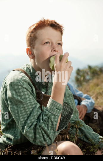 Germany, Bavaria, Boy in traditional clothing eating an apple - Stock-Bilder